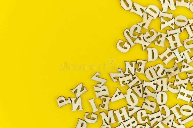 Gestaltete hölzerne lateinische Buchstaben der Draufsicht auf gelbem Hintergrund Flaches gelegtes Modell mit Kopienraum für Text stockbild
