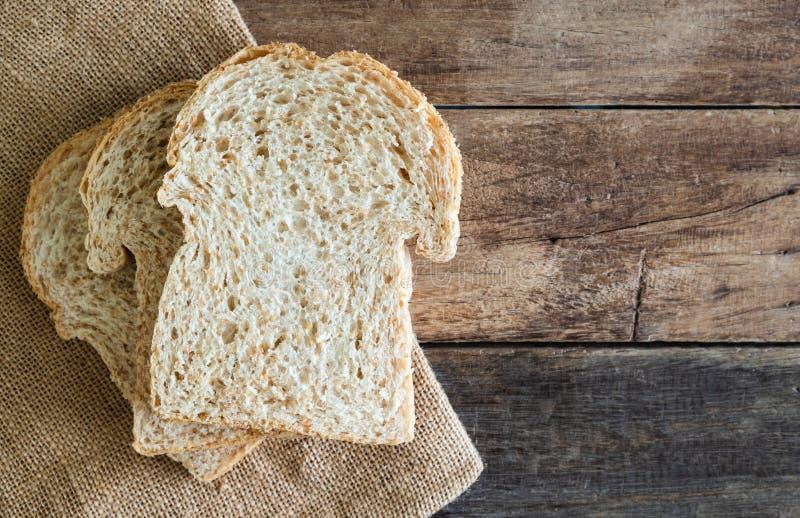 Gestapeld de sandwichbrood van de plak geheel tarwe op de doek van de jutezak op houten lijst royalty-vrije stock foto's