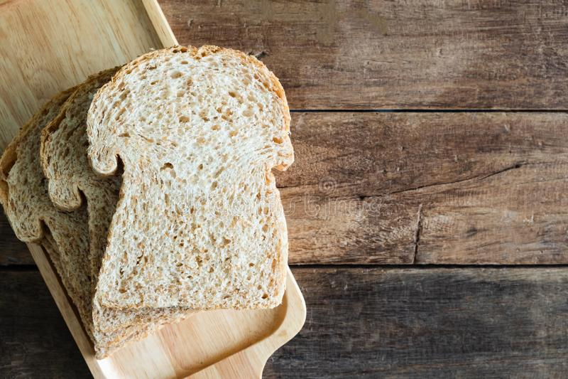 Gestapeld de sandwichbrood van de plak geheel tarwe op houten plaat op houten lijst royalty-vrije stock foto