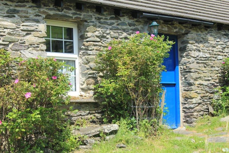 Gestapeld steenplattelandshuisje met blauwe deur in Ierland stock afbeelding