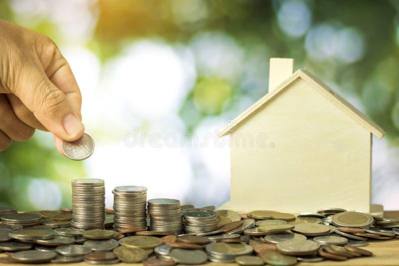Gestapeld van geldmuntstukken en houten huis op groene bokehachtergrond, royalty-vrije stock foto