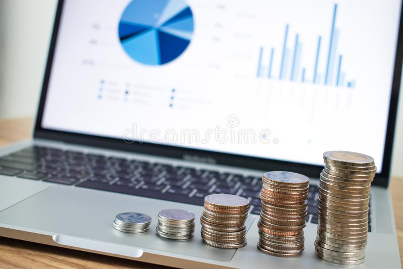 Gestapelde die muntstukken op laptop als achtergrond worden geplaatst Bedrijfs financi?nconcept stock foto's
