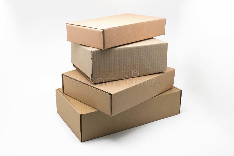 Gestapelde dozen bruin karton op een witte achtergrond, rekupereerbaar materiaal stock foto's