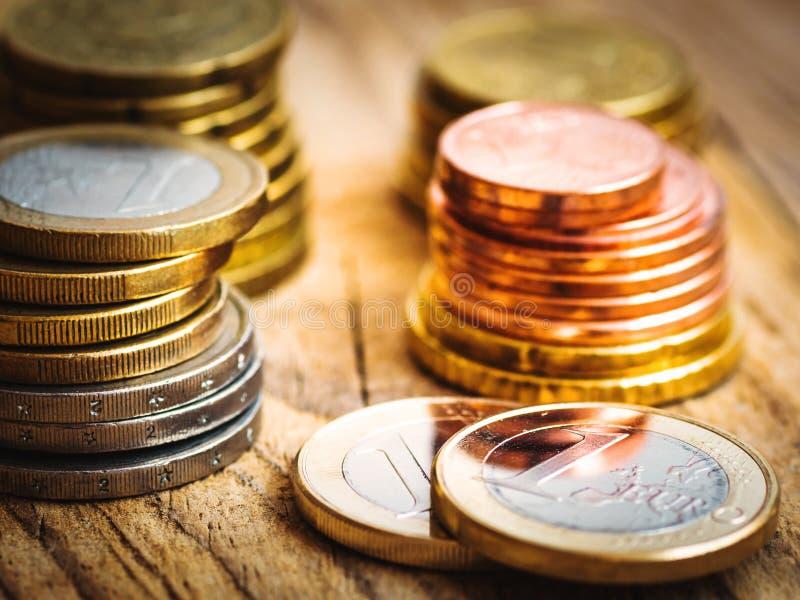 Gestapelde glanzende witte en gouden Euro muntstukken van verschillende waarde op houten achtergrond, financiën, investering, voo