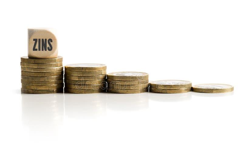 Gestapelde muntstukken die dalende rentevoeten met het woord & x22 symboliseren; interest& x22; in het Duits royalty-vrije stock foto's