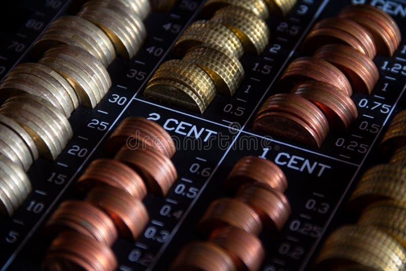 Gestapelde muntstukken in een metaalcontant gelddoos met een slot stock foto's