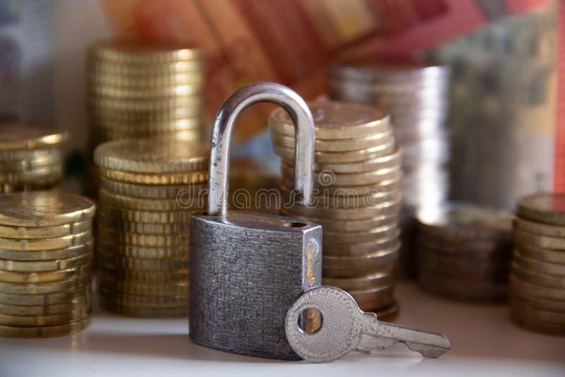 Gestapelde muntstukken en bankbiljetten achter een hangslot met een sleutel royalty-vrije stock afbeeldingen