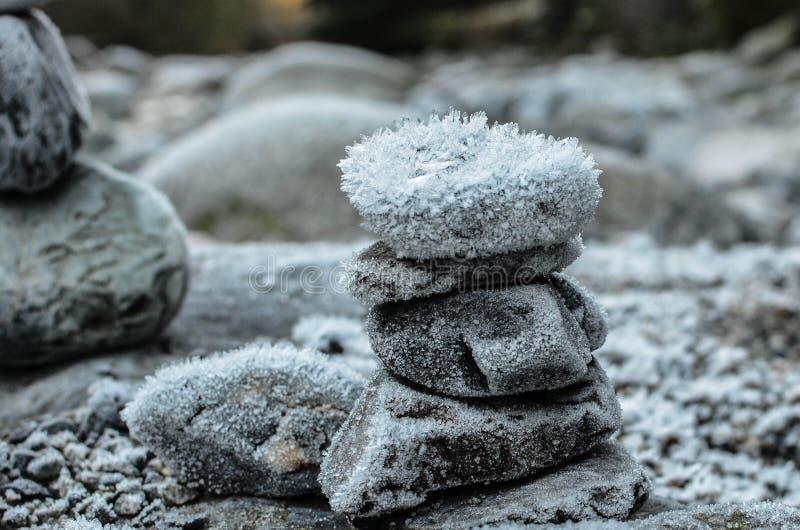 Gestapelde rotsen door de rivier in de winter stock afbeeldingen