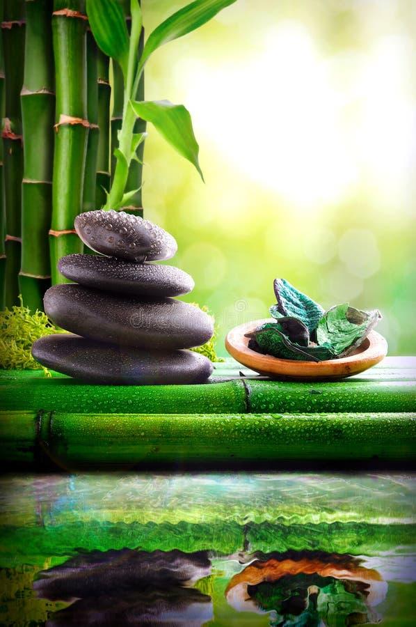 Gestapelde stenen en kom met groene die bladeren in water worden weerspiegeld royalty-vrije stock fotografie