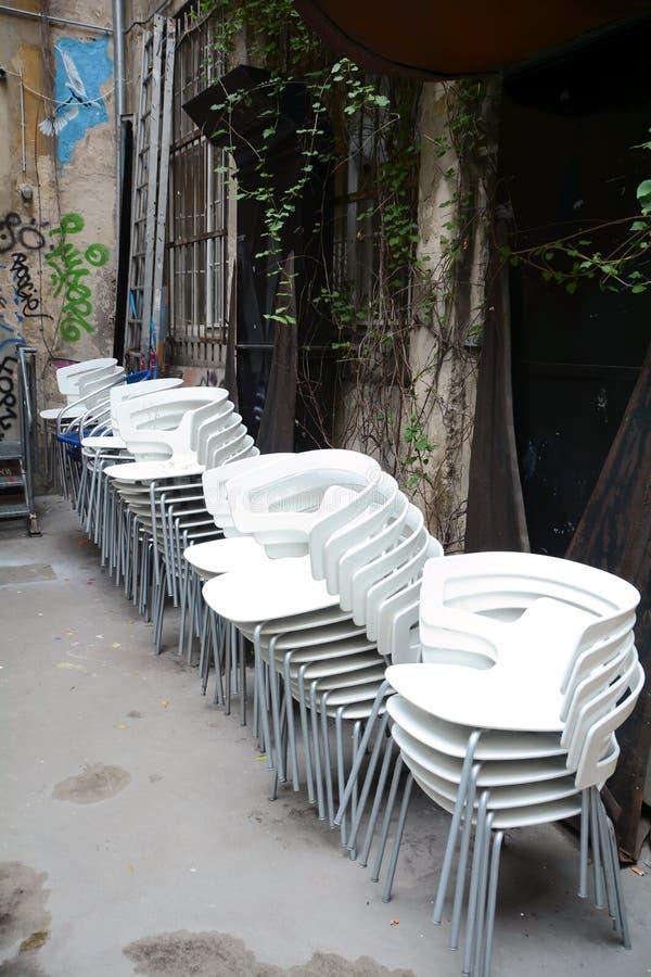 gestapelde witte stoelen in een binnenplaats stock foto's