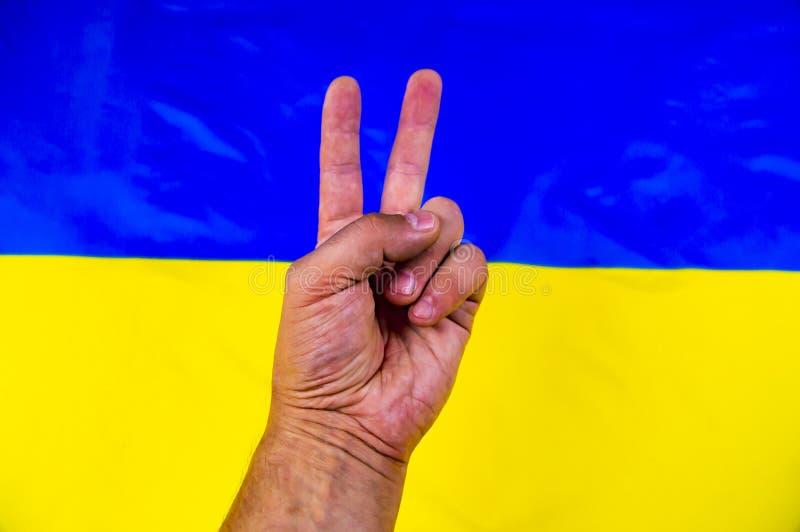 Geste de main de victoire sur le fond du drapeau ukrainien - Jour de la Déclaration d'Indépendance photographie stock