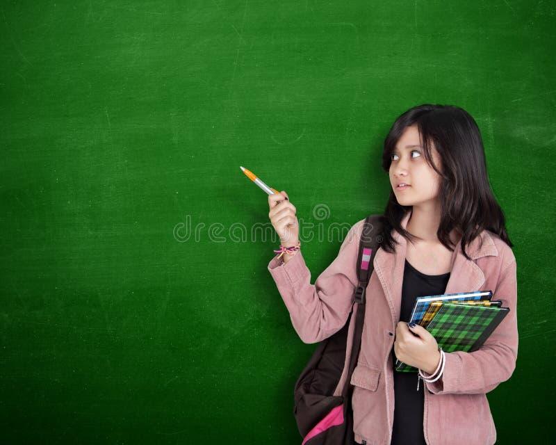 Geste de présentation de fille d'école au-dessus de tableau vert images stock