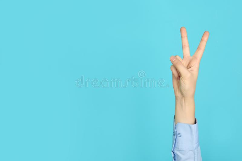 Geste de victoire d'apparence de jeune femme sur le fond de couleur photos libres de droits