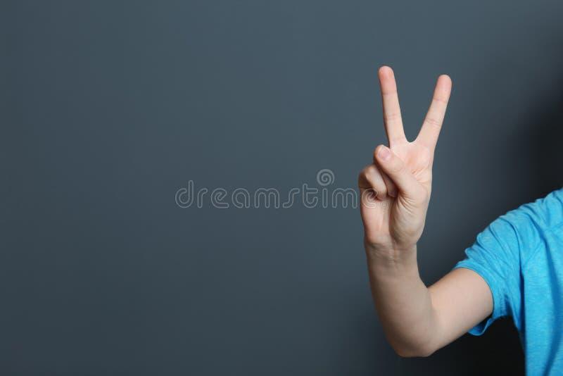 Geste de victoire d'apparence de jeune femme sur le fond de couleur photo stock