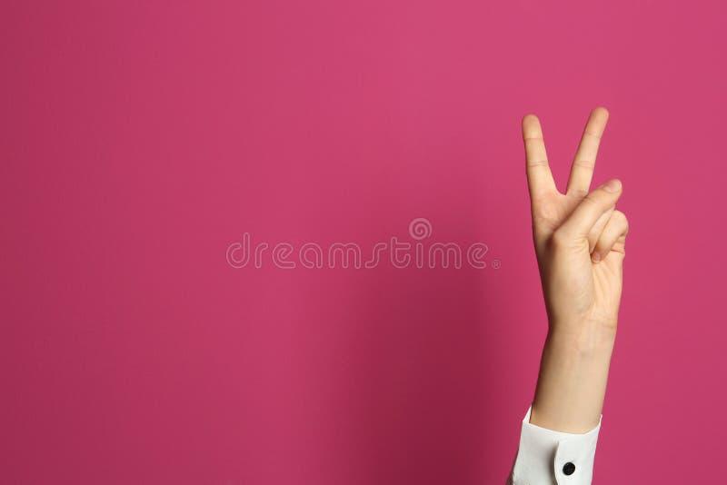 Geste de victoire d'apparence de jeune femme sur le fond de couleur image stock