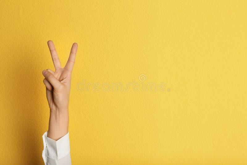 Geste de victoire d'apparence de jeune femme sur le fond de couleur photographie stock