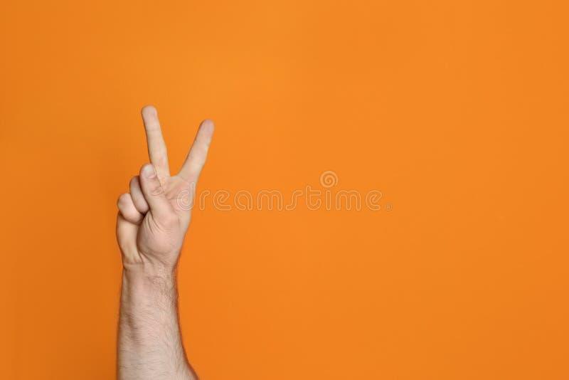 Geste de victoire d'apparence de jeune homme sur le fond de couleur photo libre de droits