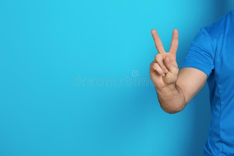 Geste de victoire d'apparence de jeune homme sur le fond de couleur images stock