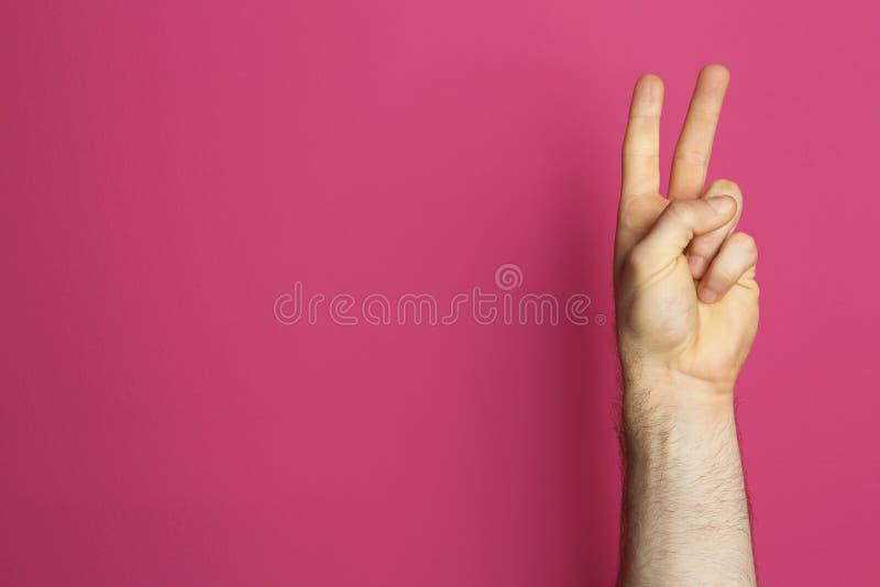 Geste de victoire d'apparence de jeune homme sur le fond de couleur images libres de droits