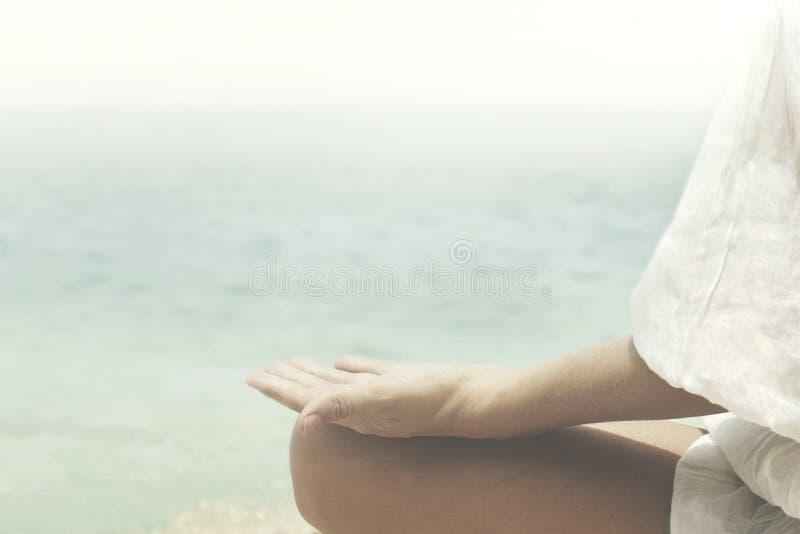 Geste de yoga des mains d'une femme faisant face à l'océan photographie stock
