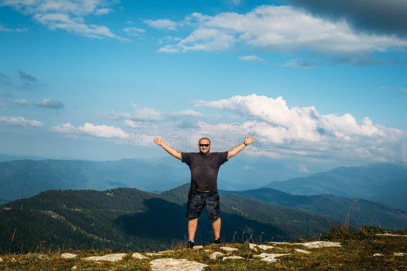 Geste heureux d'homme de triomphe avec des bras en air au fond de paysage de vallée de montagne image stock