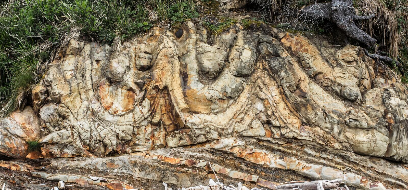 Gesteinsschichtformklippe am Strand lizenzfreie stockbilder