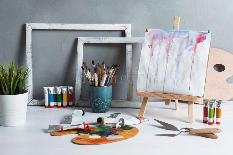 Gestell mit abstrakter Malerei und Satz Berufskunst stockbild