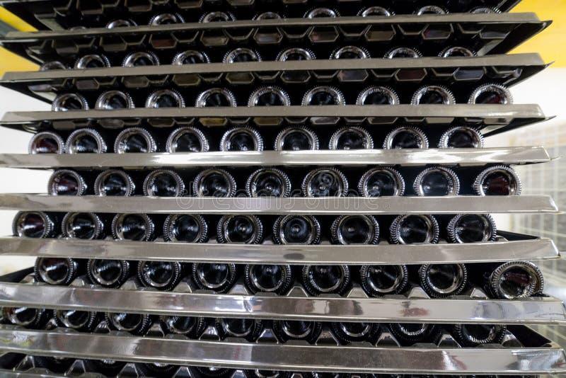 Gestelle mit Flaschen Wein liegen auf einander im Produktionsbereich stockfotos