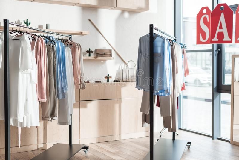 Gestelle mit Kleidung im Shop lizenzfreie stockbilder