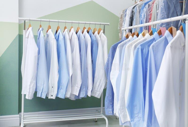 Gestelle mit sauberer Kleidung auf Aufhängern nachdem dem Chemisch reinigen lizenzfreie stockfotografie