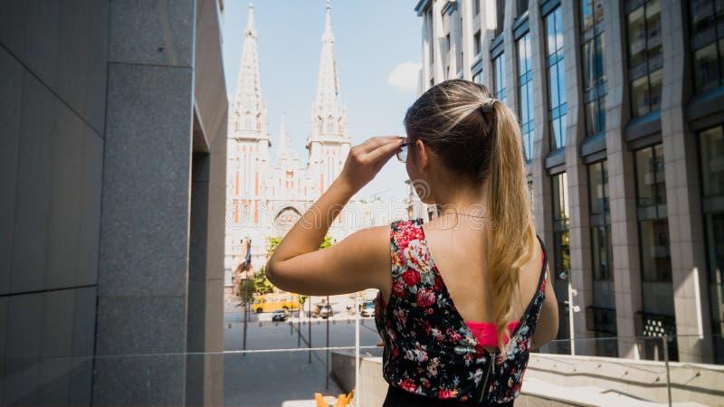 Gestemd achtermeningsbeeld van mooie jonge vrouw die met lang haar op oude katholieke cathedra kijken Het vrouwelijke toerist rei royalty-vrije stock afbeeldingen