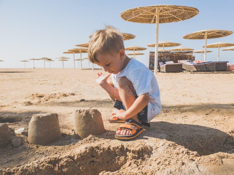 Gestemd beeld van de aanbiddelijke zitting van de peuterjongen op het zandige strand en de bouw kasteel van nat zand royalty-vrije stock afbeeldingen