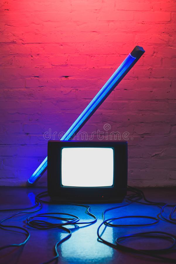gestemd beeld van geschikte retro TV-reeks, kabels en lamp met baksteen royalty-vrije stock foto's