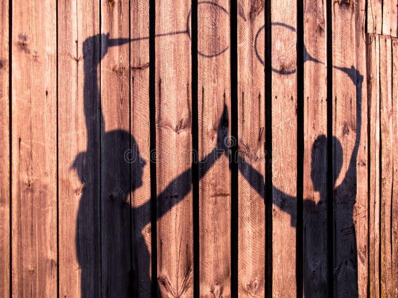 Gestemd beeld van silhouetten van mannen en vrouwen die handen met tennisrackets houden royalty-vrije stock fotografie