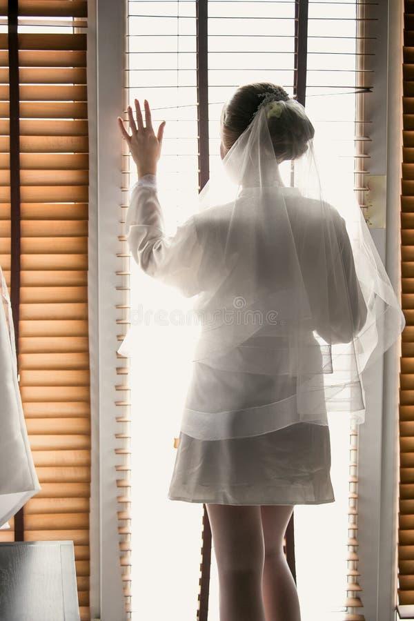 Gestemd portret van bruid het stellen bij venster en wat betreft jaloezie royalty-vrije stock afbeeldingen