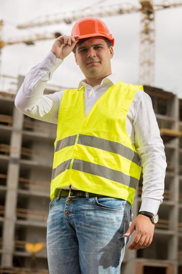 Gestemd portret van glimlachende bouwingenieur die bouwvakker dragen royalty-vrije stock foto's