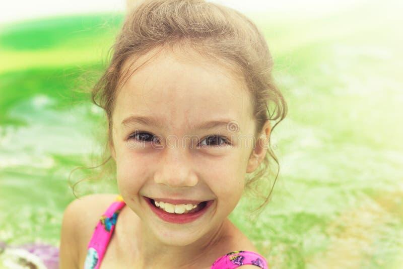 Gestemd portret van het leuke meisje zwemmen in openluchtpool stock afbeeldingen