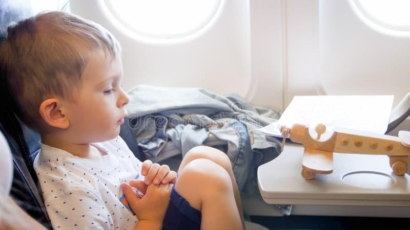 Gestemd portret van weinig jongen die op houten vliegtuigminiatuur tijdens lange vlucht kijken royalty-vrije stock fotografie