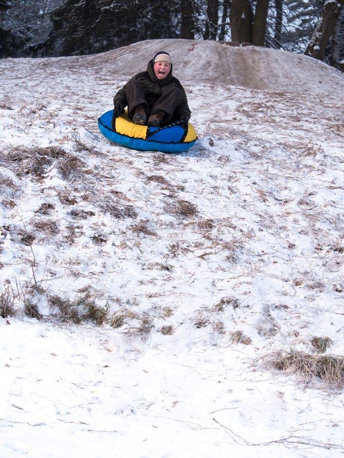Gestemde beeld gillende jongen die een slee onderaan een steile helling met sneeuw en gras berijdt royalty-vrije stock afbeeldingen