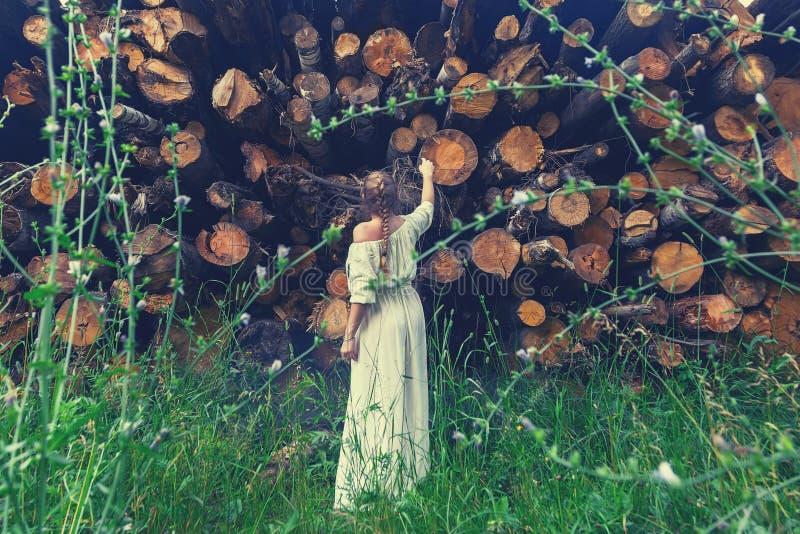 Gestemde meisjestribunes voor gezaagd onderaan bomen die hen met spijt bekijken Neem zorg en bewaar aard Achtergrond van verminde royalty-vrije stock foto's