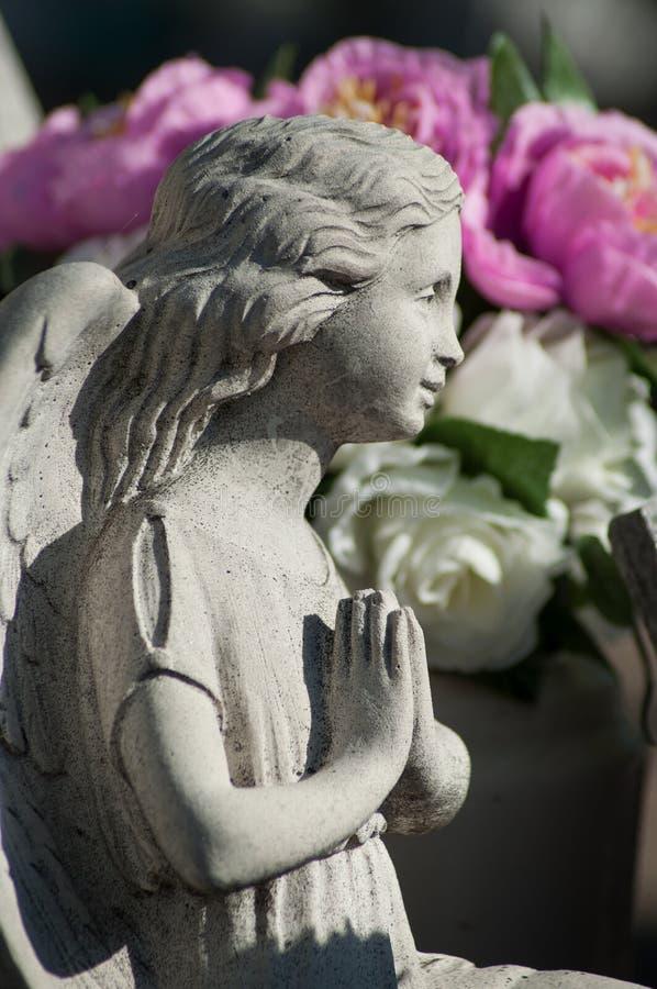 gestenigde engel die bij begraafplaats met purpere bloemen bidden royalty-vrije stock afbeeldingen