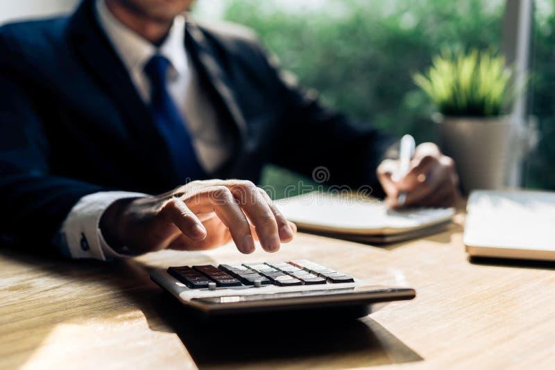 Gestión accouting del hombre de negocios con la calculadora fotografía de archivo libre de regalías