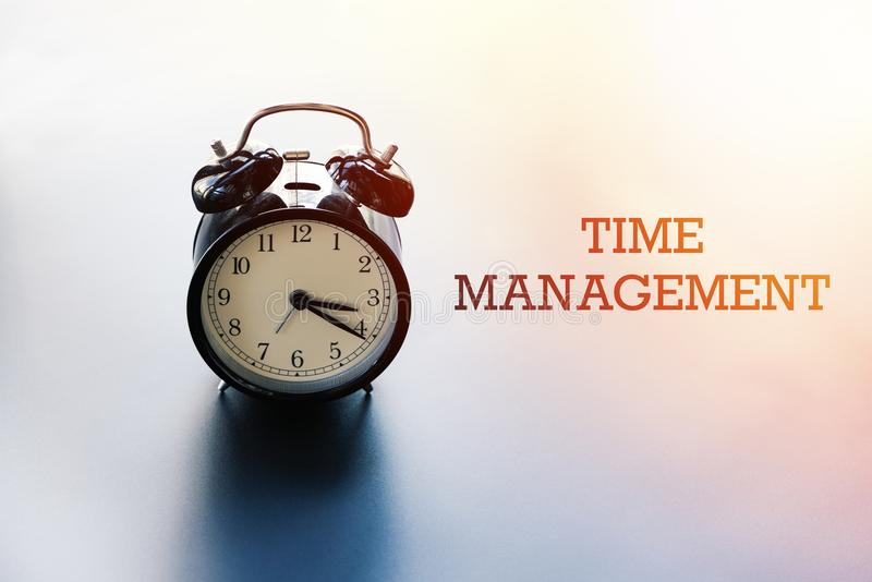 Gestión de tiempo, concepto de la balanza de la vida del trabajo, despertador con la GESTIÓN de palabras TIEMPO foto de archivo libre de regalías