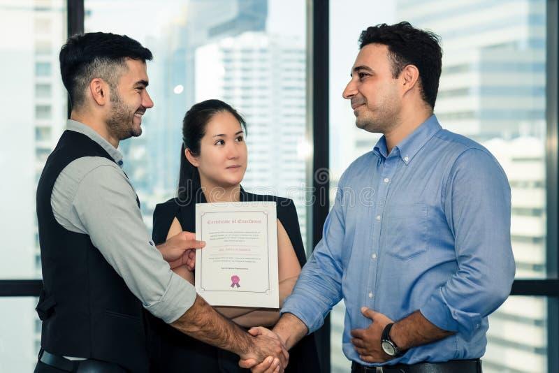 Gestión ejecutiva que tiene enhorabuena al personal ejecutivo que consigue el premio con el certificado de excelencia fotografía de archivo libre de regalías