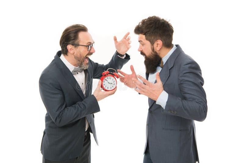 Gesti?n de tiempo hombres barbudos maduros en despertador formal del control del traje plazo Tarde otra vez Hombres de negocios e imagen de archivo libre de regalías