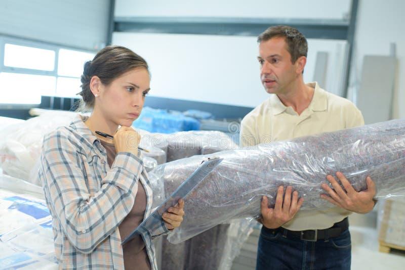 Gesticulando o trabalhador fêmea do escritório que fala ao colega de trabalho fotografia de stock