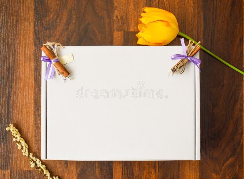 Gestileerd het model digitaal dossier van de Voorraadfotografie leeg kartonvierkant met houten vloerachtergrond met gele tulp, le royalty-vrije stock afbeeldingen