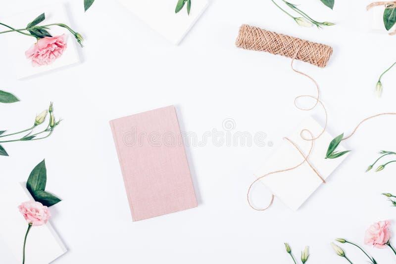 Gestileerd vrouwelijk bureau met roze boek in het centrum stock afbeelding