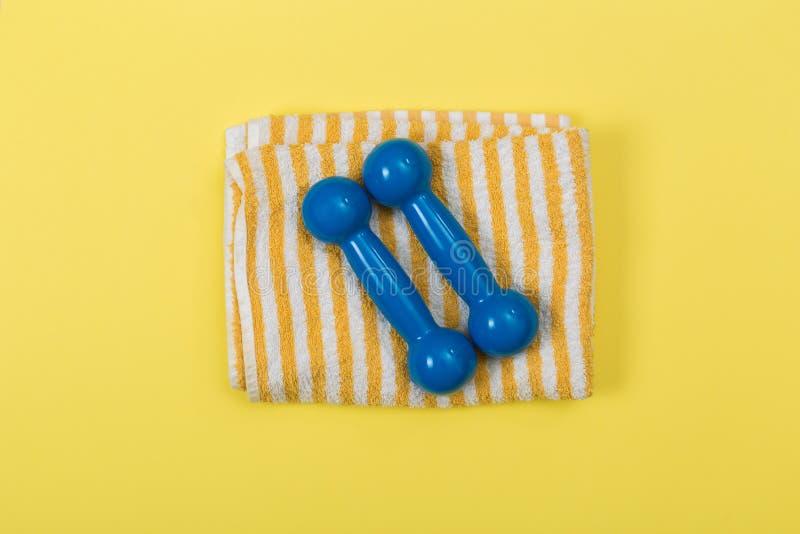 Gestileerde fotografie van de domoren en de handdoek van het geschiktheidsmateriaal op gele achtergrond royalty-vrije stock foto's