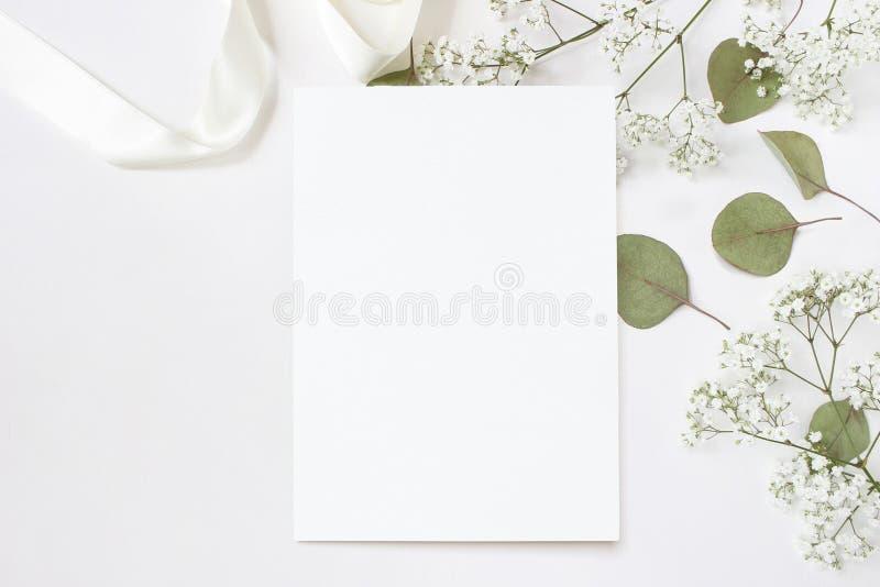 Gestileerde voorraadfoto Vrouwelijk de kantoorbehoeftenmodel van de huwelijksdesktop met lege groetkaart, baby` s adem Gypsophila stock afbeeldingen